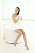 Woman sitting on bathtub ledge drying her hair with a towel