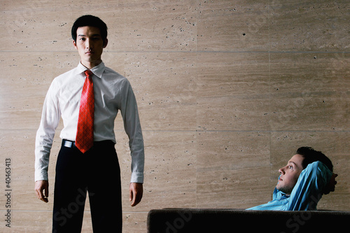 One businessman standing while the other one relaxing on the couch.