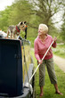 Senior woman looking at her dog while mopping her houseboat