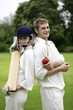Man and woman holding a cricket bat and a cricket ball