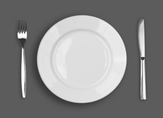 Knife, white plate and fork on gray background