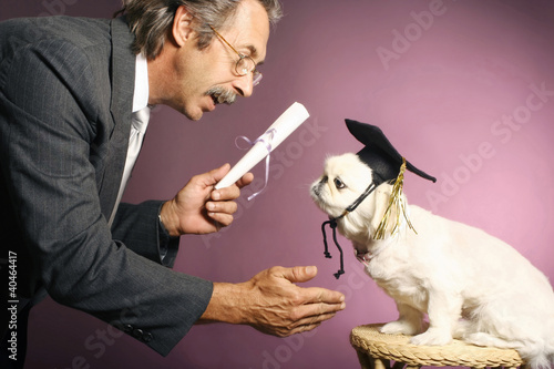Senior man presenting a scroll to his dog