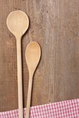 2 Kochlöffel und Serviette auf einem Holzbrett