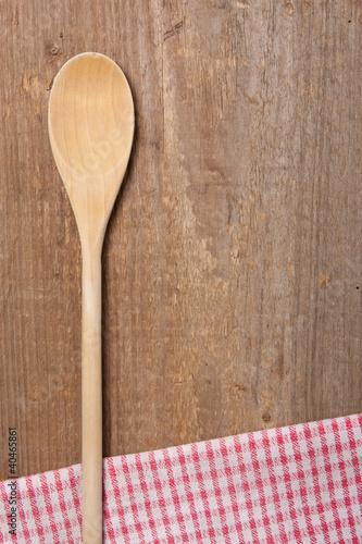Kochlöffel und Serviette auf einem Holzbrett