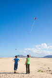 mother and son fly a kite at natural reserve dunes of Corralejo,