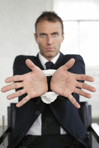 Businessman sitting on chair with his wrist tied up