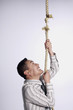 Businessman climbing a tearing rope