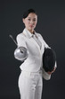 Businesswoman holding fencing mask and thrusting a fencing foil