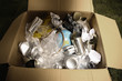 Cardboard box filled with plastic bottles, tin cans, papers, rope and a globe