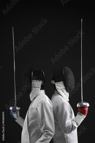 Two men leaning back to back holding fencing foils