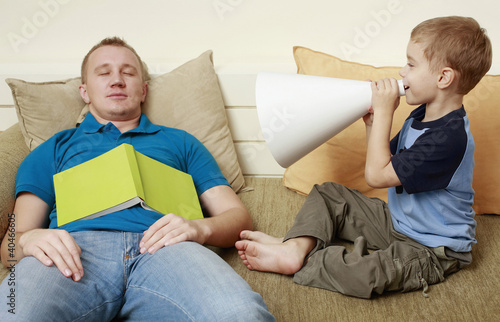 Man sleeping on couch, boy screaming through megaphone