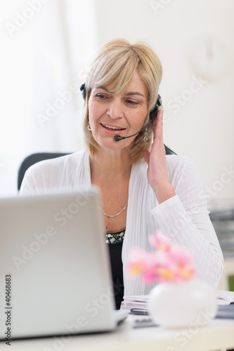 Middle age business woman with headset working on laptop
