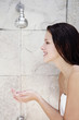 Woman cupping water from the shower