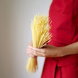 Side view of a lady in red apron holding some spaghetti