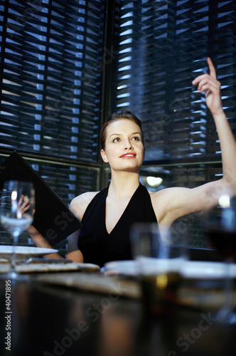 Woman raising her hand to order her food in a restaurant