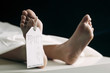 Toe tag hanging on woman lying on table in morgue