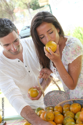 Cheerful couple choosing fruits in outdoor market