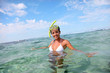 Smiling woman in water with snorkeling outfit