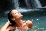 Fototapety Beautiful woman enjoying bathing near natural waterfall