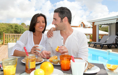 Cheerful couple taking breakfast on the outdoor terrace