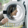 Woman loading clothes into the washing machine