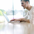 Man smiling while using laptop