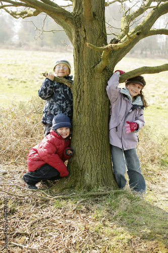 Children posing by a tree