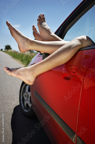 Legs hanging out of the car