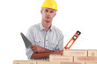 Tradesman holding up a bubble level and a trowel