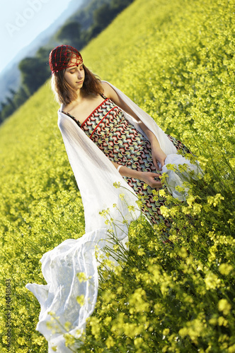 Dreaming Young Woman standing in the Rape Field