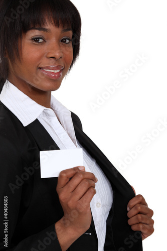 Woman pulling out a business card from her blazer