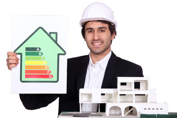Architect holding model house and energy rating poster
