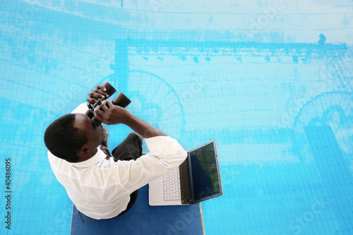Businessman sitting on starting block using binoculars