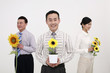 Business people holding sunflowers