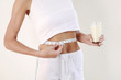 Woman with measuring tape around her waist holding a glass of milk