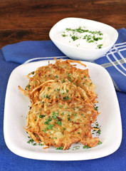 Potato Latkes and sour cream, vertical.