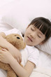 Girl sleeping and hugging soft toy