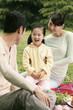 Girl and parents having picnic in the park