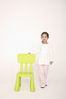 Girl standing next to a green chair