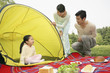Girl sitting in the tent, man and woman looking at her