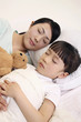 Woman and girl sleeping, girl hugging soft toy