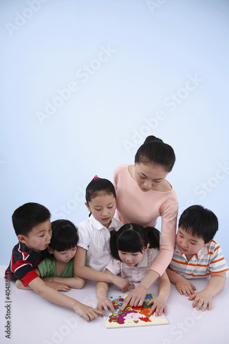 Woman teaching children with a map