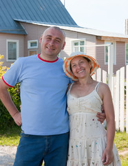 adult man and woman near gate of  home
