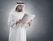 arabian businessman shocked while reading newspape