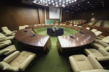 Auditorium with round oak table and beige armchairs around it