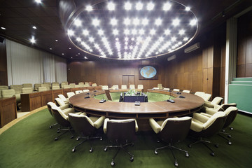 Auditorium with round oak table, beige armchairs around it