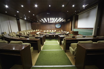 Auditorium with  round oak table and beige armchairs around it.