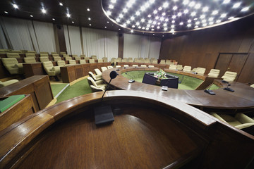 View on the auditorium with round oak table and beige armchairs