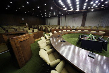 Conference hall with round table and rows of chairs