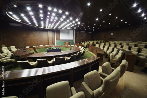Auditorium for the meeting with round table, rostrum and chairs